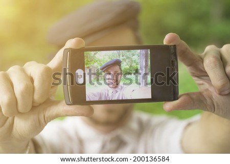 Young man with cap taking self with phone