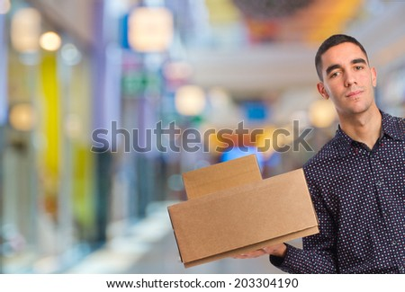 young man with cardboard boxes in a shopping center - stock photo