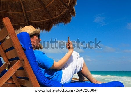 young man with cell phone on tropical beach vacation - stock photo