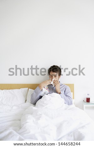 Young man with cold blowing nose in bed - stock photo