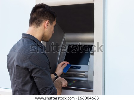 Young man with credit card at the ATM