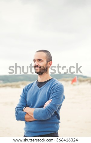 Young man with crossed arms relaxing on the beach - stock photo
