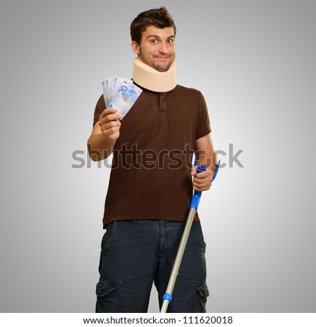 Young Man With Crutches Holding Note On Gray Background - stock photo