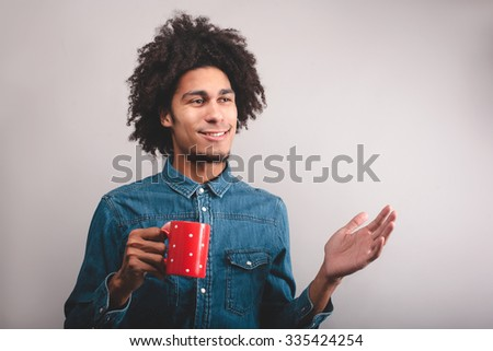 young man with cup of tea greeting someone - stock photo