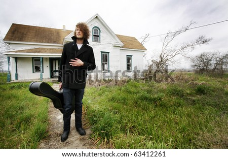Young man with curly hair standing in front of an abandoned house holding a guitar case.