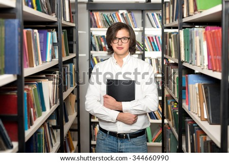 young man with dark hair standing and holding a black copy book and a note pad between book shelves in the library, looking in front of him, front view, a concept of studying