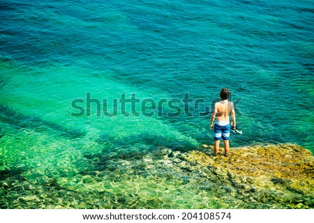 Young Man with Diving Mask Standing in Clear Sea. Healthy Lifestyle Concept. Summer Vacation. Copy Space. - stock photo