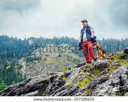 Young man with dog outdoors - stock photo