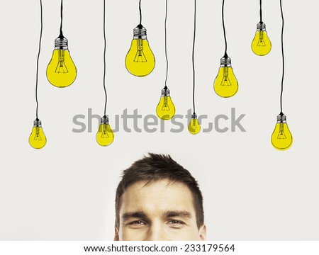 young man with drawing bublbs on wall - stock photo