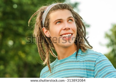 Young man with dreadlocks against summer garden. - stock photo