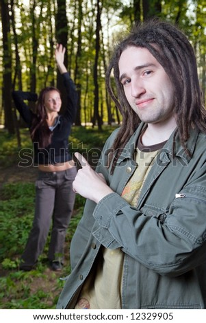 Young man with dreadlocks and girl in a forest