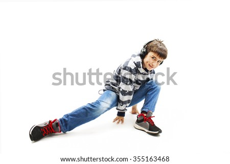 Young man with ear-phones dancing hip-hop. Isolated on white background - stock photo