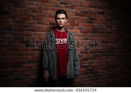 Young man with earphones listening to music wearing cap against white brick wall - stock photo
