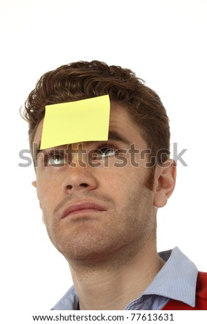 young man with empty post it on his forehead - stock photo
