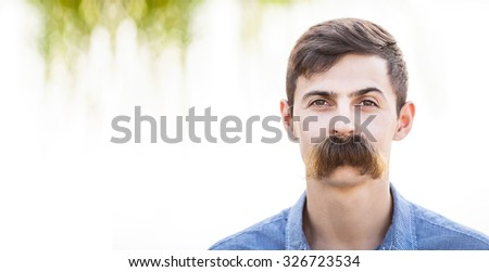 Young man with fake mustaches. Dental health concept. - stock photo