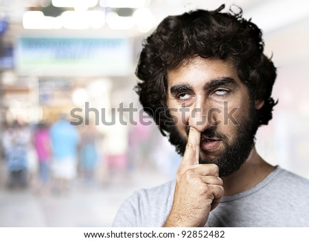 young man with finger in his nose at a crowded place - stock photo