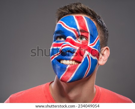 Young man with flag painted on his face to show UK support in sports. - stock photo