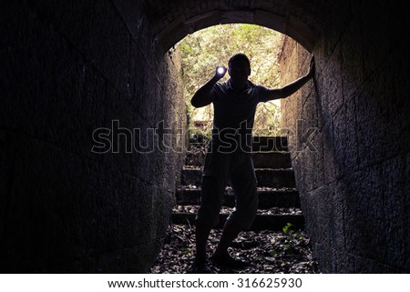 Young man with flashlight enters dark stone tunnel and looks inside, tonal correction photo filter effect - stock photo