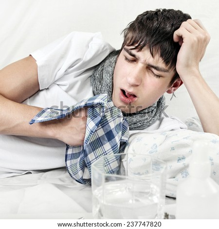 Young Man with Flu on the Bed with Handkerchief