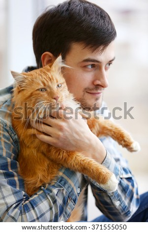 Young man with fluffy red cat looking out the window