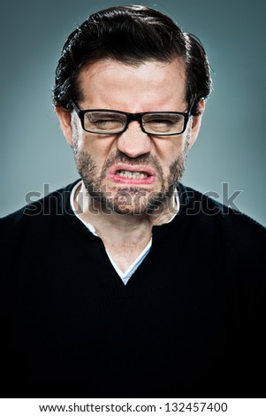 Young Man with Furious Expression Over a Grey Background