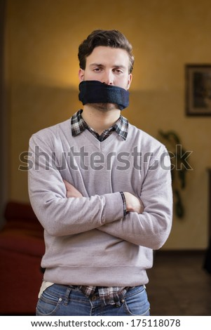 Young man with gag (scarf) on his mouth cannot speak - stock photo