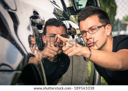 Young man with glasses inspecting a luxury car before a second hand trade - stock photo