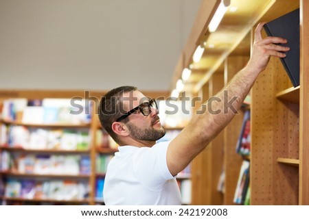 Young man with glasses picking a book in a library - stock photo