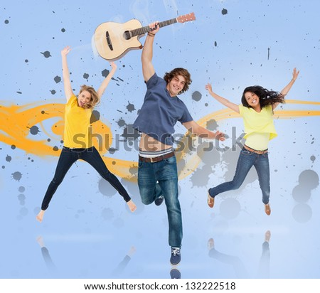 Young man with guitar and two girls jumping for joy with yellow smoke trail and grey paint splatters on blue background