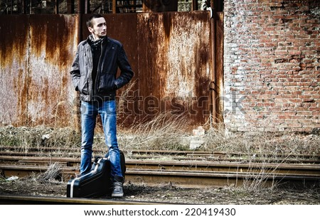 Young man with guitar case waiting for the train among industrial ruins  - stock photo