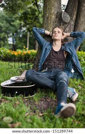 young man with guitar in summer park