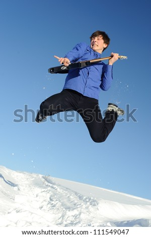 Young man with guitar jumping in a snow field