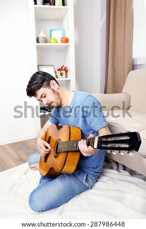 Young man with guitar on floor in room - stock photo