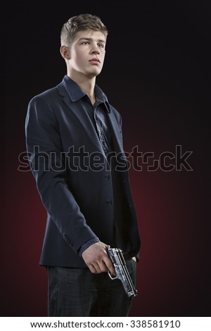 Young man with gun. Dark red background. Standing portrait. - stock photo