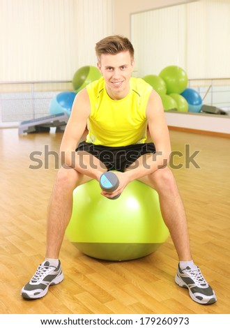 Young man with gymnastic ball in gym