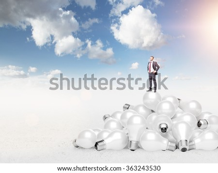 Young man with hands in pockets standing on a heap of huge scattered bulbs, proud of himself. Blue sky at the background. Concept of new ideas. - stock photo