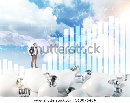 Young man with hands in pockets standing on huge scattered bulbs, proud of himself. Blue sky and graphs at the background. Concept of new ideas.