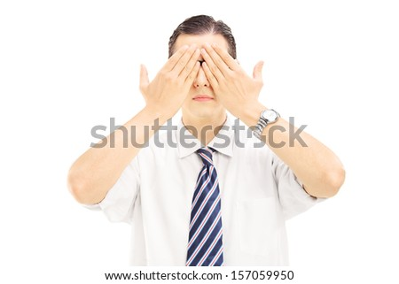 Young man with hands over his eyes isolated on white background - stock photo