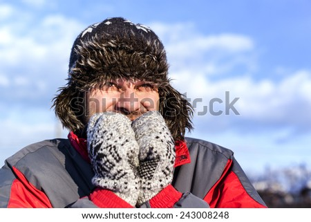 Young man with hat and coat shivering from cold in winter - stock photo