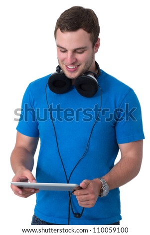 Young man with headphones and blue t-shirt working on a tablet pc - stock photo