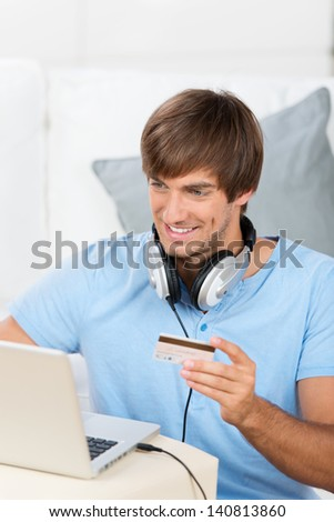 young man with headphones buing music with laptop - stock photo