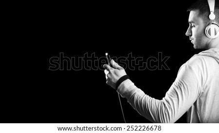 Young man with headphones enjoying with good music. Black and white. Black background - stock photo