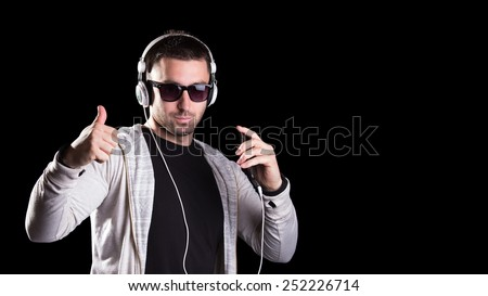 Young man with headphones enjoying with good music. Black background - stock photo