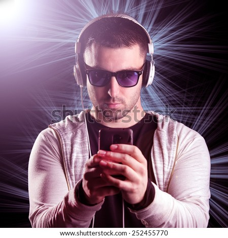 Young man with headphones enjoying with good music. Disco atmosphere, lens flare, laser light - stock photo