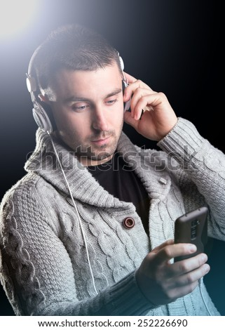 Young man with headphones enjoying with good music. Lens flare. Black background - stock photo
