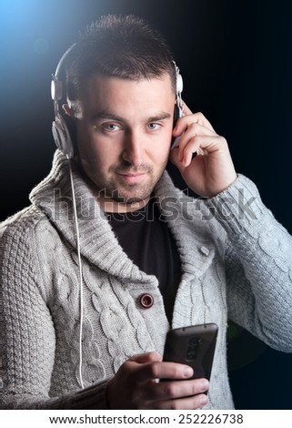 Young man with headphones enjoying with good music. Lens flare. Black beckground - stock photo