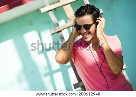 Young man with headphones listening music on a urban background - stock photo
