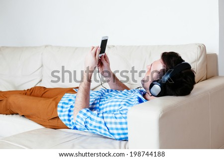Young man with headphones lying on a sofa and listening to music - stock photo