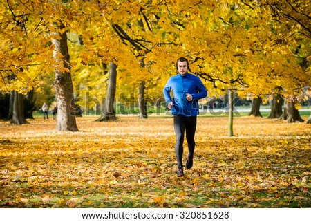 Young man with headphones running in autumn nature and listening music - stock photo