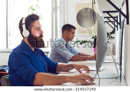 Young Man with Headphones working on a Computer - stock photo